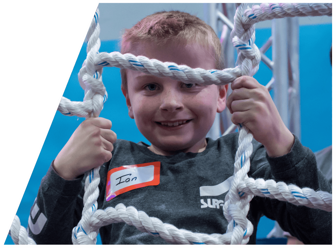 A young boy smiling on a rope ladder at The Warrior Factory