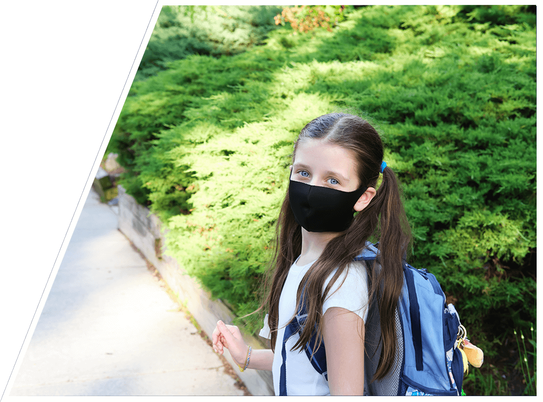 A young girl with a backpack and mask on